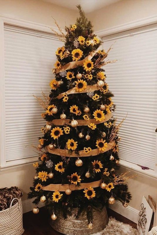 a Thanksgiving tree with ribbons, sunflowers, shiny metallic ornaments and branches is a fun rustic idea