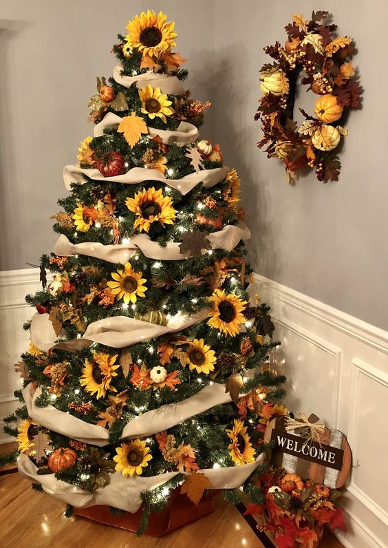 a Thanksgiving tree with tan ribbons, lights, sunflowers, leaves and pumpkins topped with a sunflower