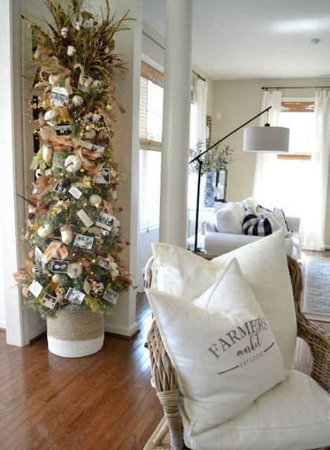 a Thanksgiving tree with white pumpkins, acorns, leaves, lights, pinecones, grasses and family pics is very cute