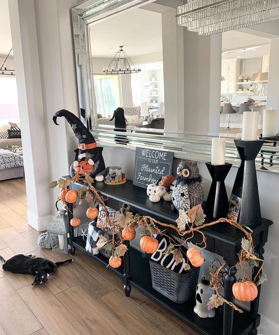 a black console with branches with pumpkins, leaves, white pumpkins, candles, witches' hats is awesome for Halloween