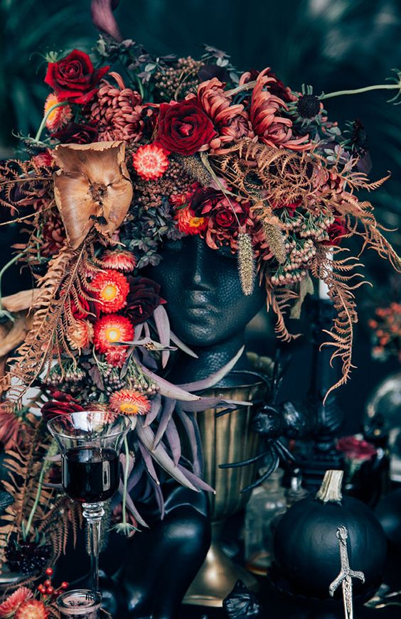 a black head vase with a very lush and bright floral arrangement with red, pink, burgundy blooms, black ones, dried leaves and herbs