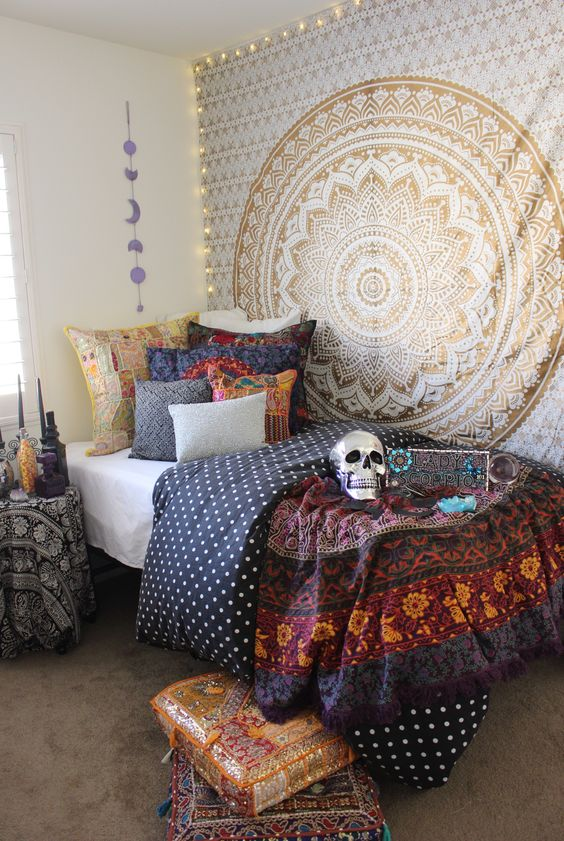 a boho Halloween bedroom with a mandala hanging, bold and dark bedding, bright sequin cushions, a metallic skull and black candles