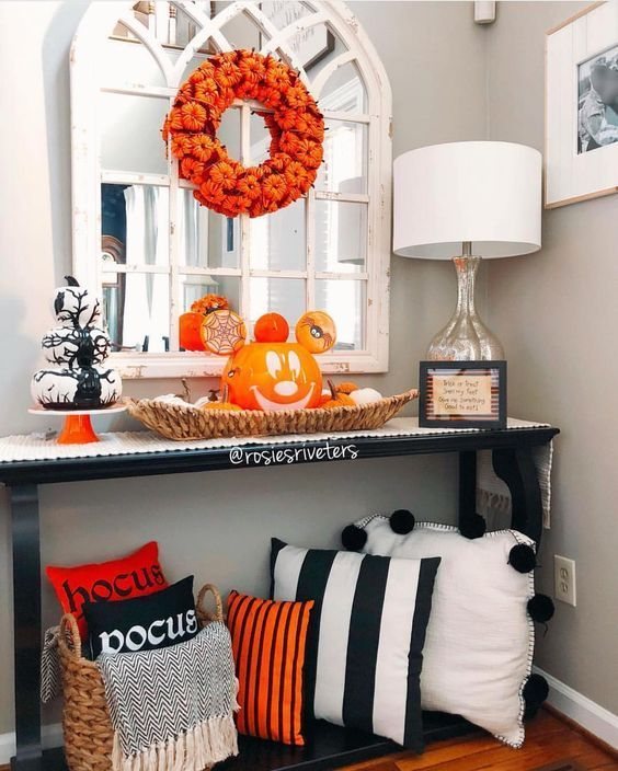 a bold Halloween console table with striped pillows, a basket tray with a jack o lantern, a pumpkin wreath and a pumpkin stack