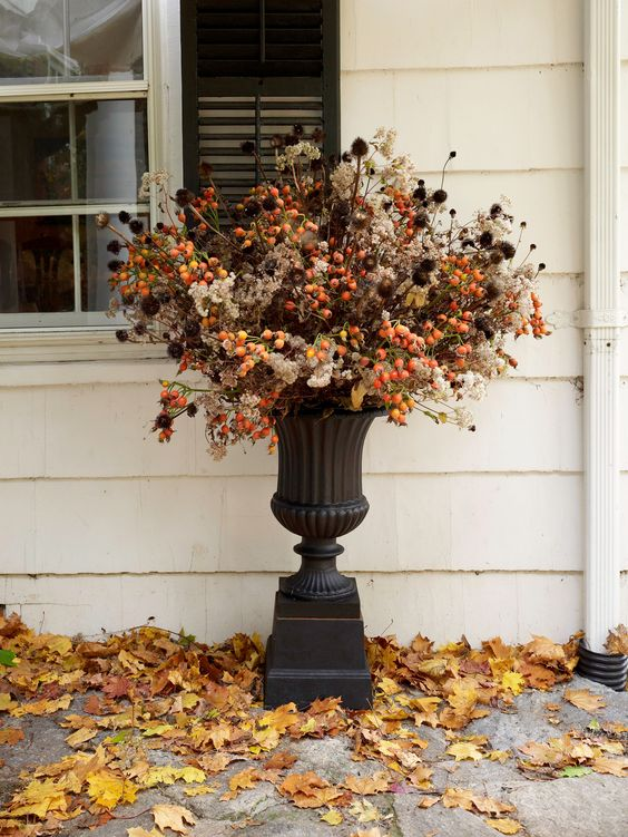 a bold outdoor floral arrangement for Halloween done with berries and dried blooms and foliage
