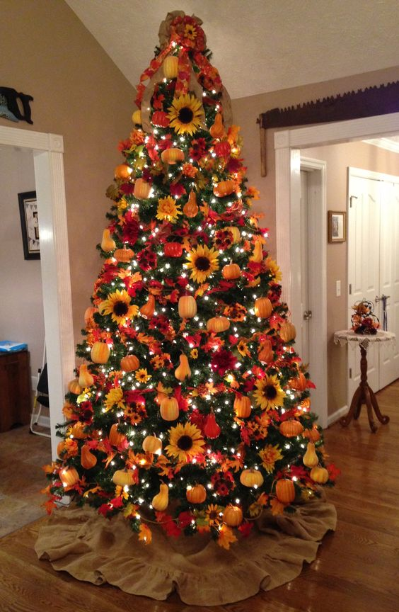 a bright fall tree with lights, plaid ribbons, faux pumpkins, pears, sunflowers and a red bow on the top