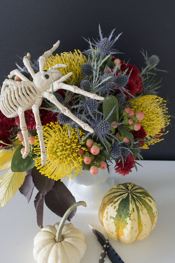 a bright floral arrangement with mustard, red blooms, berries and thistles plus a large spider on top