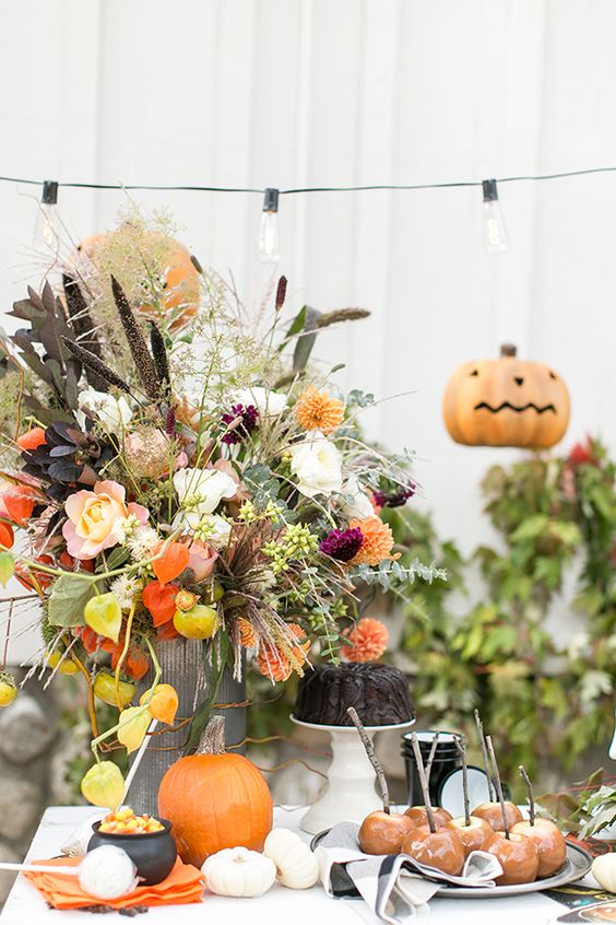 a bright rustic Halloween centerpiece with fresh peachy, orange and dried blooms, dark and usual foliage and greenery