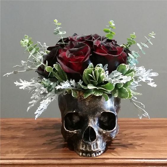 a bronze skull vase with eucalyptus, greenery and deep colored roses as a Halloween centerpiece