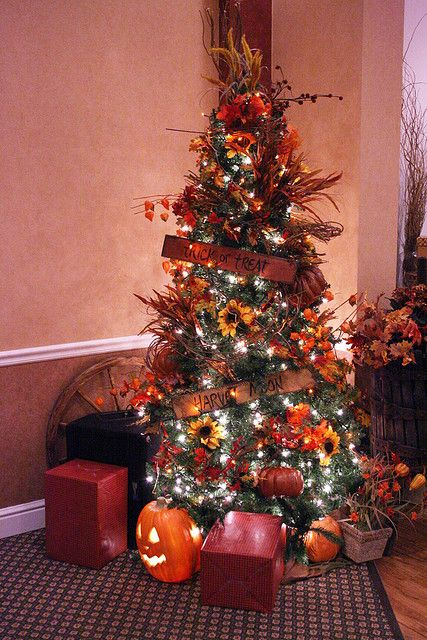 a chic Thanksgiving tree with lights, sunflowers, pumpkins, dried grasses and leaves plus some signs