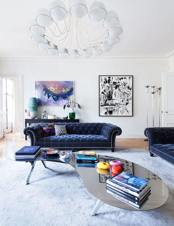 a chic contemporary French space with two navy velvet Chesterfield sofas, a curvy mirror table and bold artworks