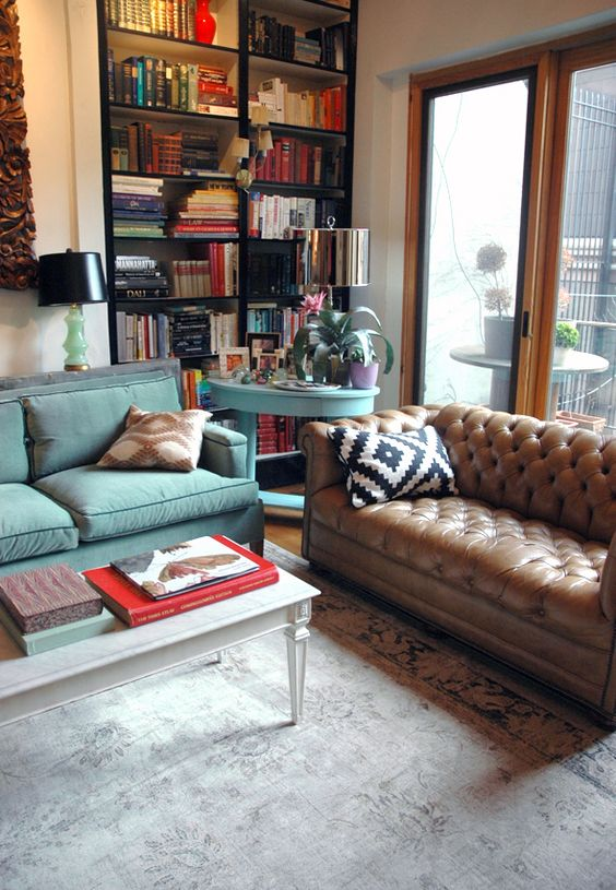 a contemporary living room with a brown leather Chesterfield sofa, a powder blue one and a matching table, lots of books and lamps