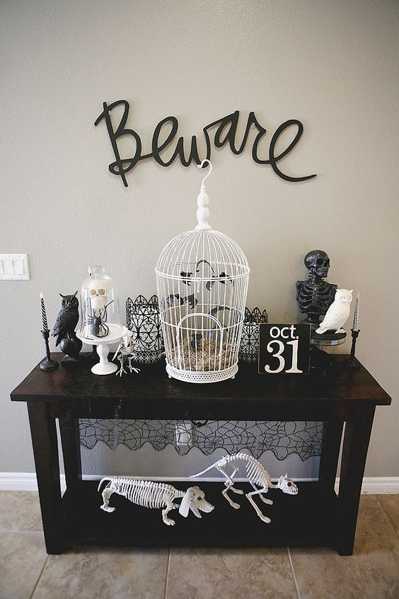a contrasting Halloween console with cages, candleholders, a skeleton, some birds and animal skeletons