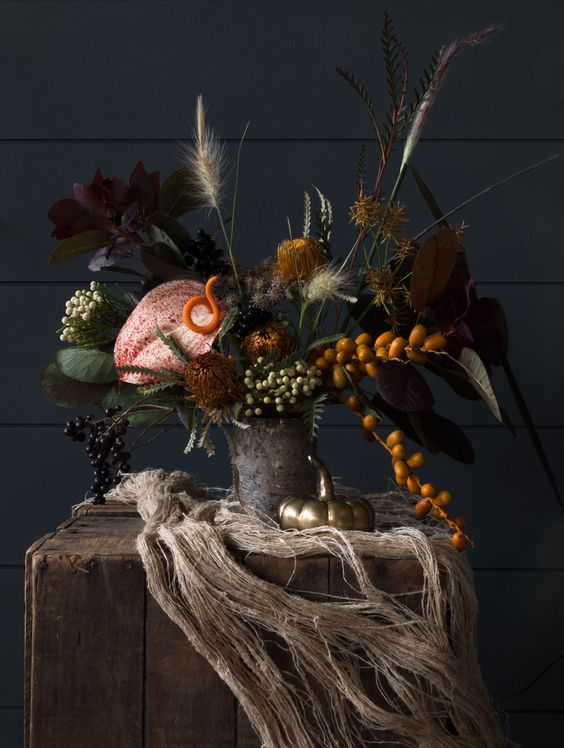 a creepy floral Halloween centerpiece with dark foliage, grasses, kumquats, berries and leaves