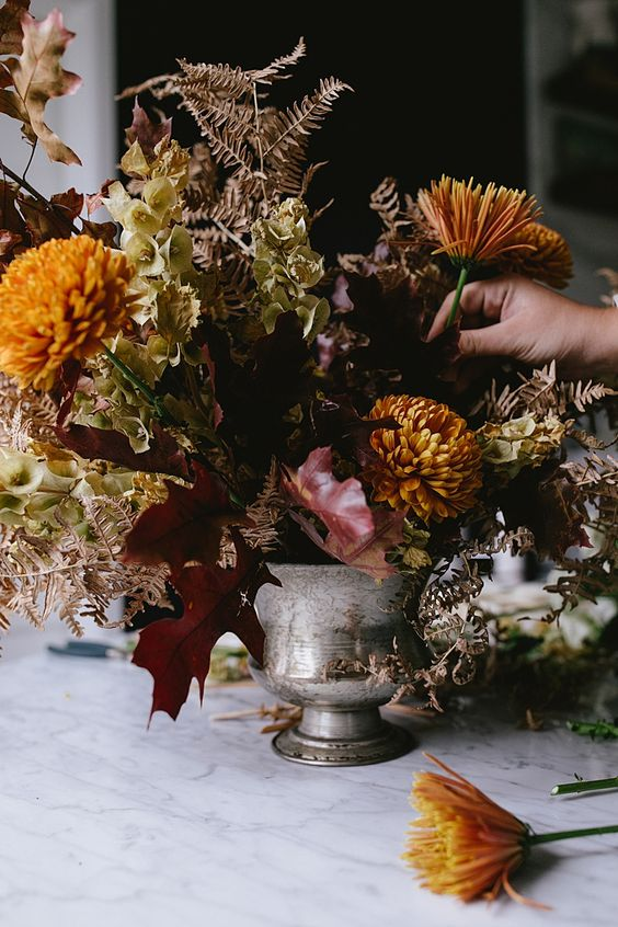 a dark and moody floral centerpiece of a silver urn, rust and mustard blooms, dried leaves and bright fall leaves