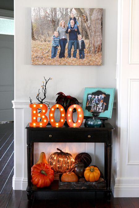 a dark stained console with faux pumpkins, a lit up pumpkin, marquee letters, branches and a photo