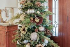 a fabulous Thanksgiving tree with white, silver and velvet pumpkins, greenery, pinecones, antlers and some more pumpkins under it