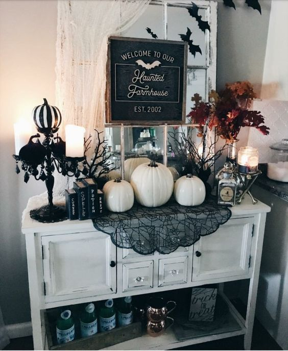 a farmhouse console with white pumpkins, black lace, a black candelabra, candles and a chic sign for Halloween