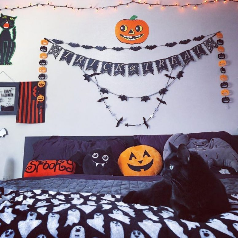 a fun and whimsy Halloween bedroom with bat and pumpkin garlands, lights, a black bed with fun pillows and plushies