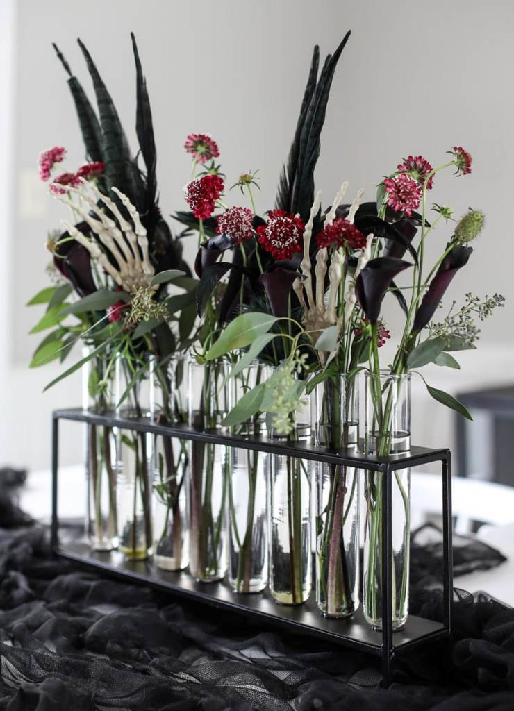 a gorgeous Halloween floral arrangement of red, pink and deep purple blooms, greenery, feathers and skeleton hands
