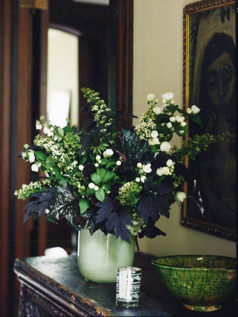 a green vase with greenery, white blooms and dark foliage for a rustic or natural Halloween tablescape