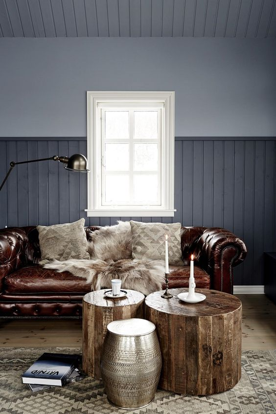 a grey living room with a brown leather Chesterfield sofa, wooden stools and a metal one, candles and a lamp