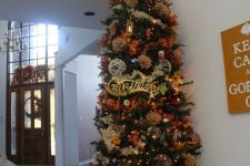 a large Thanksgiving tree with lights, twine balls, faux leaves, blooms, grasses and fabric flowers is extra bold