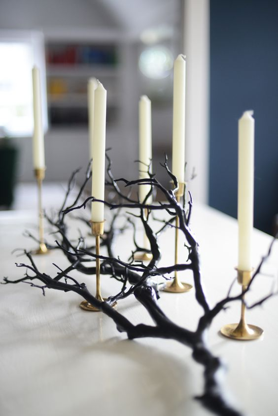a minimalist Halloween centerpiece of a black branch and white candles in gold candleholders is easy to recreate