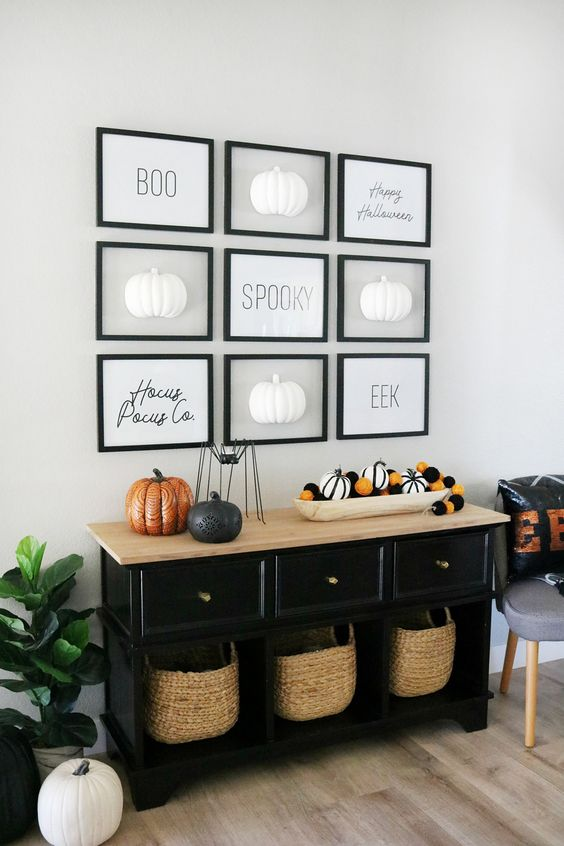 a minimalist Halloween gallery wall with letters and half pumpkins in black frames