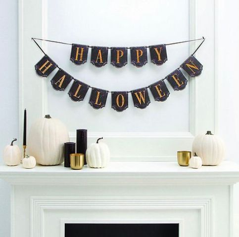 a minimalist Halloween mantel with a black and orange banner, white pumpkins and black candles in gold candleholders