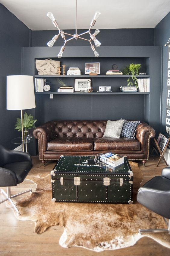 a modern home office with a brown leather Chesterfield sofa, black chairs, a chest table and a faux animal skin rug