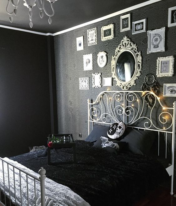 a moody Halloween bedroom in black, with a scary gallery wall, a mirror and some cool spooky pillows