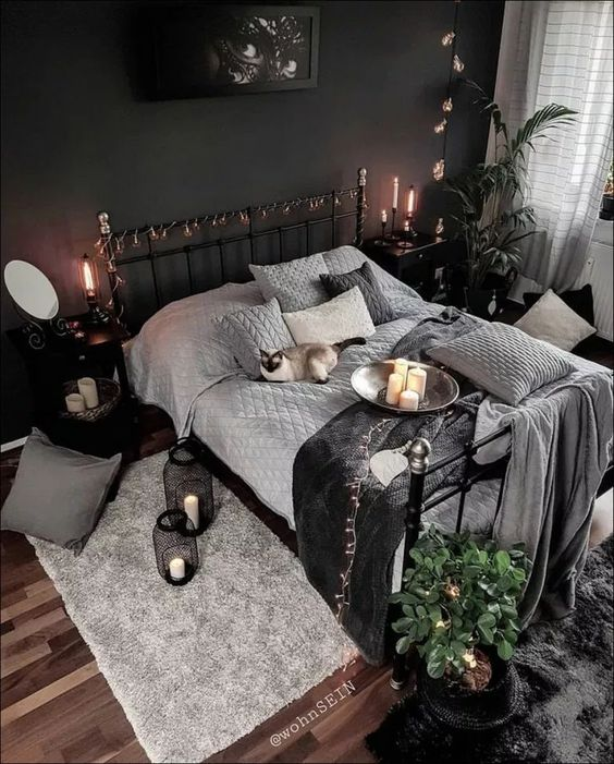 a mysterious artwork, some lights, candles in black candleholders and lanterns and moody textiles make the bedroom Halloween-like
