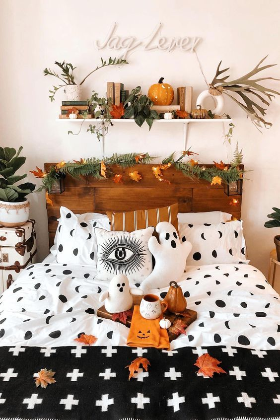 a natural Halloween bedroom with a fern and leaf garland, lights, leaves, spooky bedding and pillows, ghosts and pumpkins