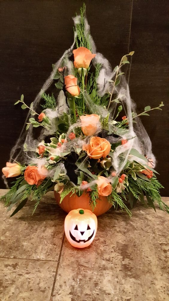 a pumpkin vase with greenery and bright orange blooms covered with spiderwebs is a chic floral arrangement for Halloween