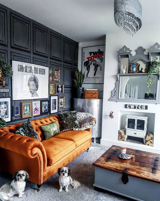 a quirky living room with an orange Chesterfield sofa, a hearth and firewood, a bold gallery wall and mirrors