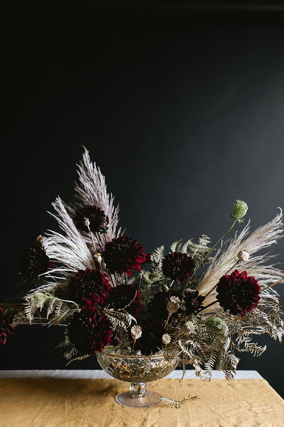 a refined Halloween floral arrangement with dark dahlias, dried blooms, leaves and grasses is a very stylish idea