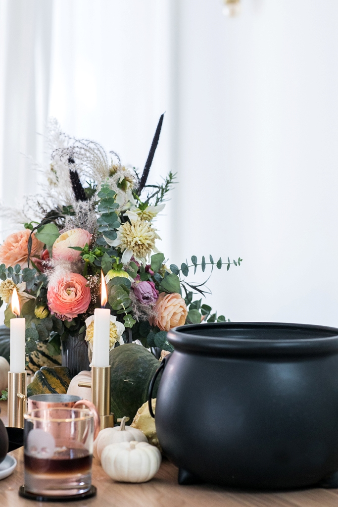a refined floral Halloween centerpiece with peachy and pink blooms, dried blooms and grasses and much eucalyptus