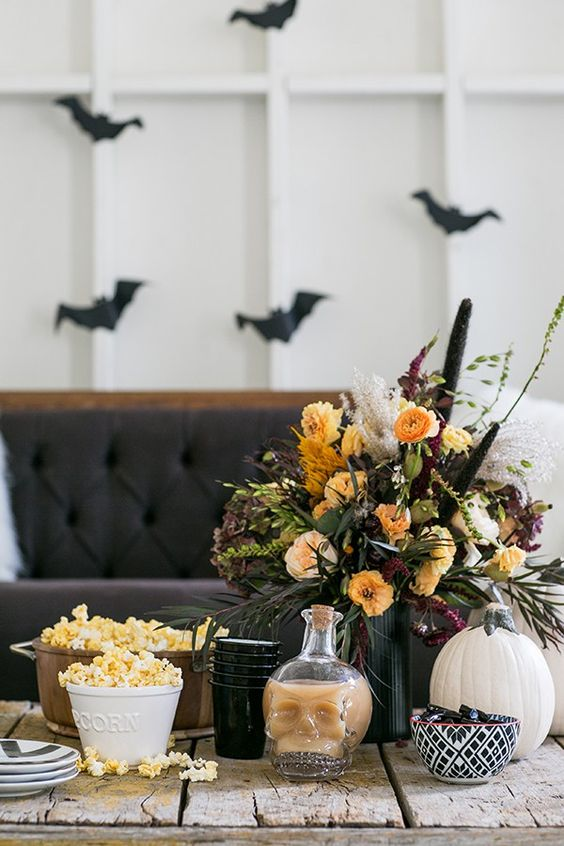 a refined moody Halloween centerpiece with yellow and orange blooms, greenery, grasses and catchy textures