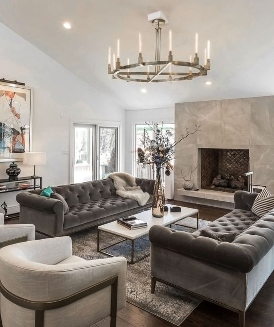 a refined neutral living room with a fireplace, grey Chesterfield sofas, neutral chairs, a modern chandelier