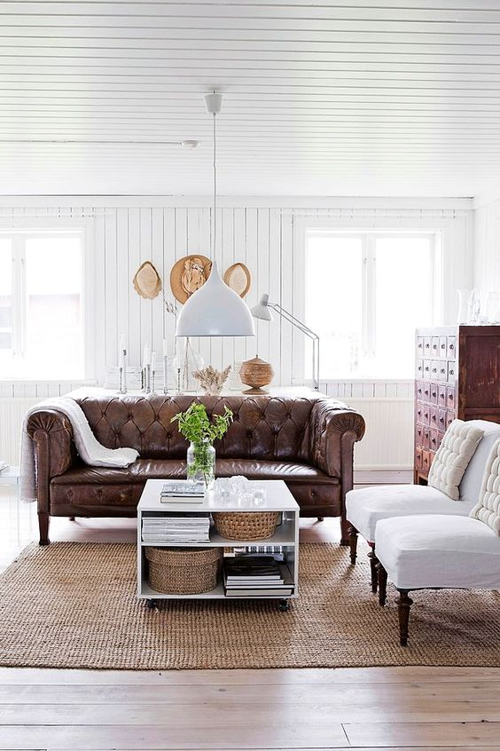 a refined rustic living room with a brown leather Chesterfield sofa, a vintage apothecary cabinet and white chairs