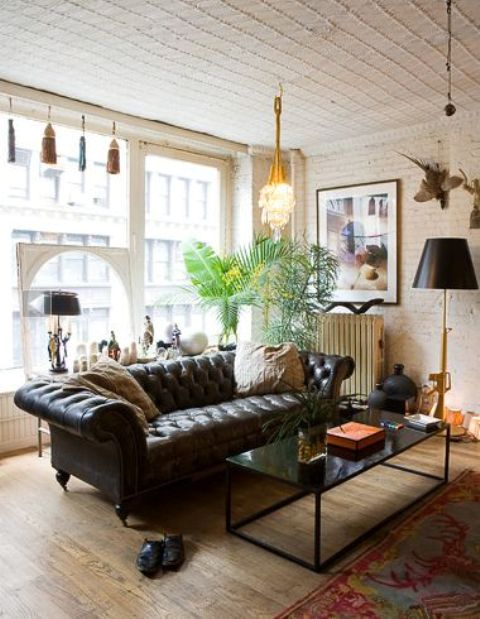 a refined space with a brown leather Chesterfield sofa, a black table and lamps for bold accenting