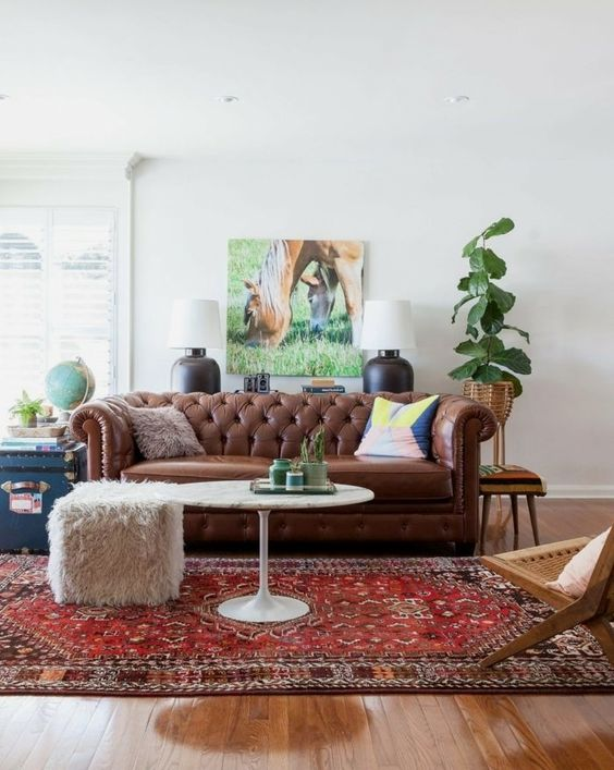 a relaxed living room with a brown leather Chesterfield sofa, a woven chair, a fur stool and some plants