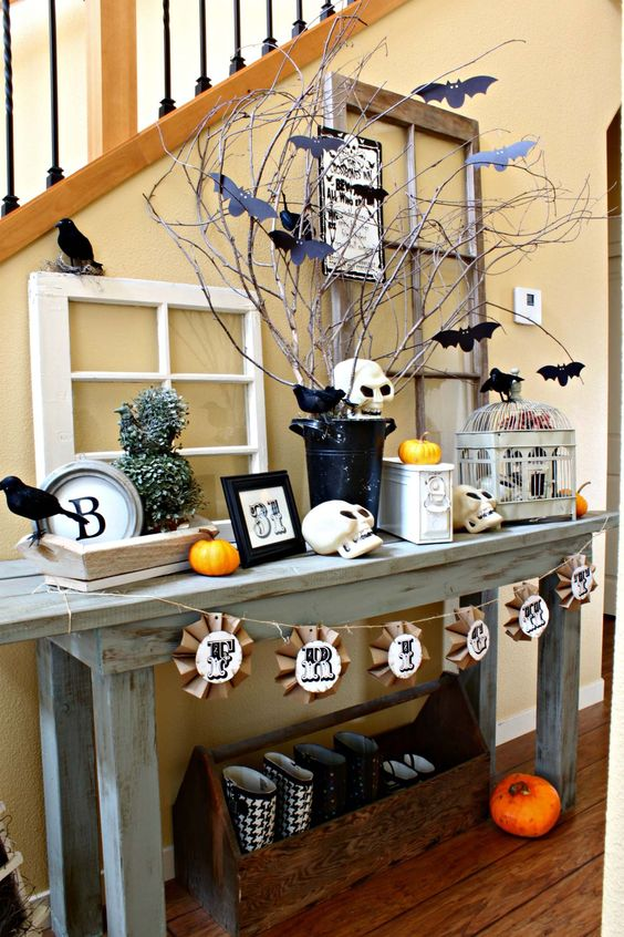 a rustic vintage Halloween console styled with skulls, a paper garland, pumpkins, blackbirds, bats and a cage