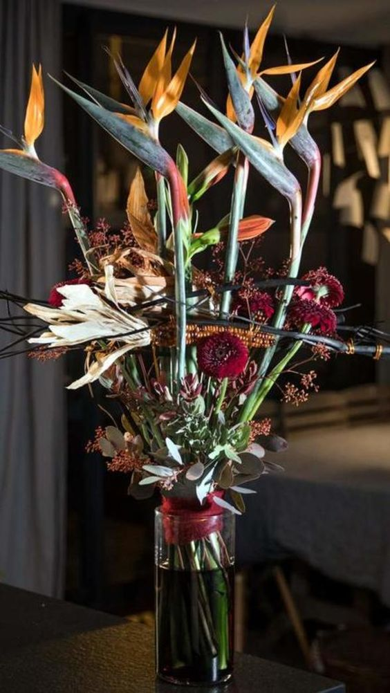 a scary Halloween floral arrangement with orange and burgundy blooms and greenery plus corn cobs