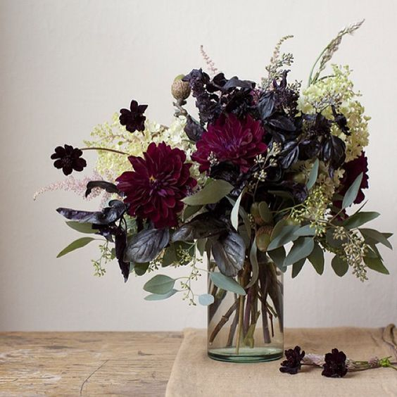 a simple dark floral arrangement of deep purple and white blooms, eucalyptus and dark foliage for Halloween