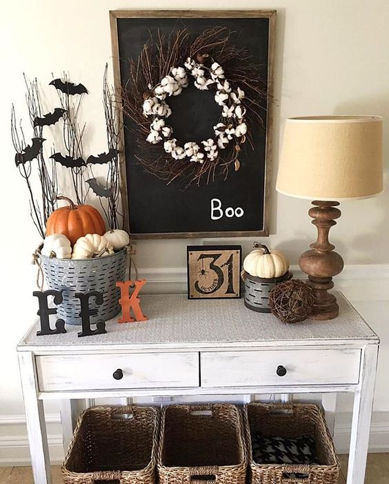 a simple rustic Halloween console with a cotton wreath, letters, pumpkins, bats on twigs, a vine ball and a vintage sign