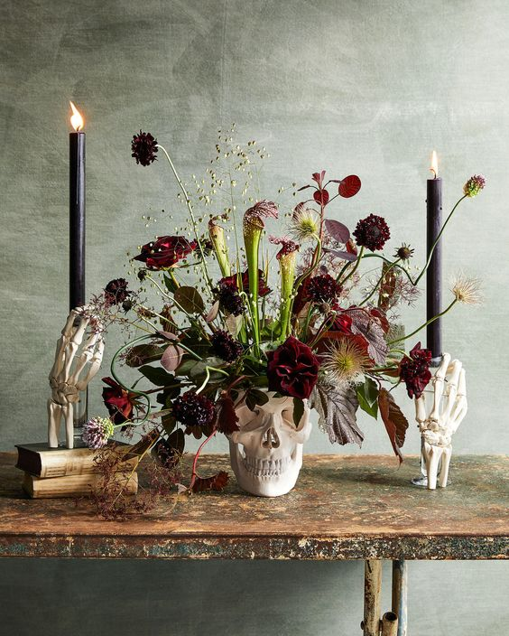 a skull vase with burgundy blooms, dark and usual leaves, greenery and black candles for Halloween