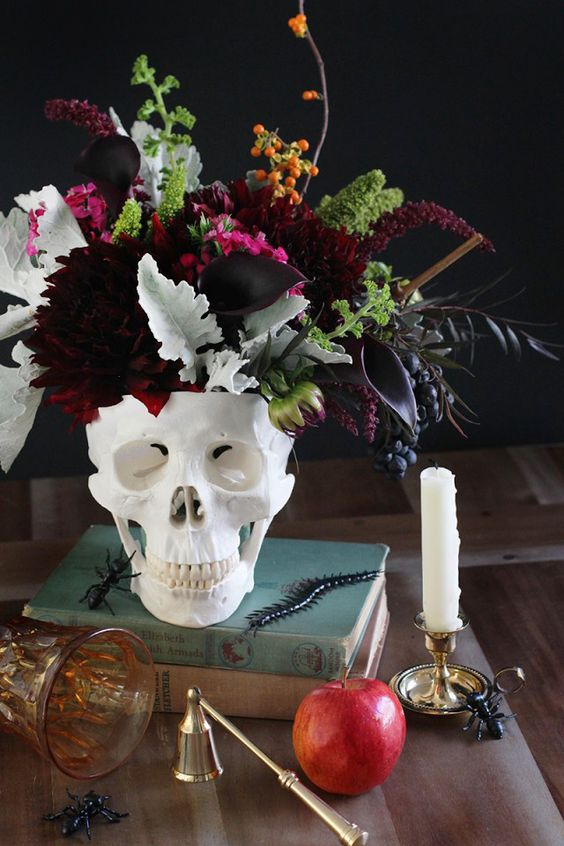 a skull vase with dark dahlias, callas, greenery, berries and some dark foliage is a stunning Halloween centerpiece