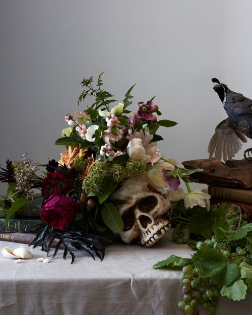 a skull with blush, burgundy, pink blooms, greenery, berries and moss for stylish Halloween decor