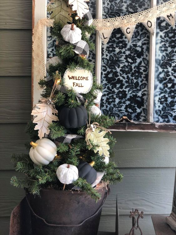 a small fall tree with white and black pumpkins, paper leaves, a plaid ribbon and some lights can fit Thanksgiving, too